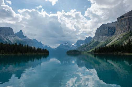 Crystal clear lake reflecting clouds and mountains against a blue sky symbolizing Cloud Innovation.